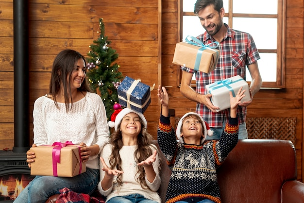 Medium shot parents surprising kids with gifts Free Photo