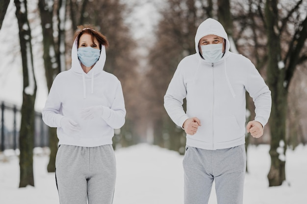 Среднего кадра люди бегут в масках Бесплатные Фотографии