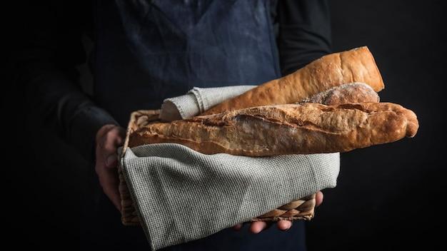 Persona del colpo medio che tiene pane Foto Gratuite