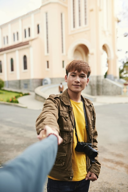 Medium shot portrait of an asian guy with photo camera holding hand of unrecognizable woman Free Photo