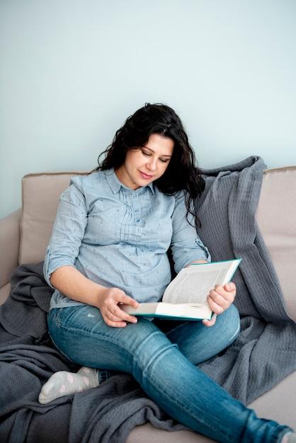 Medium shot pregnant woman reading a book Free Photo