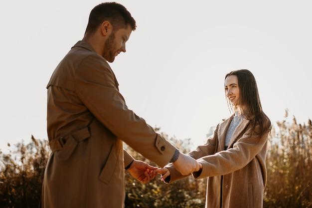 Coppie romantiche del colpo medio che tengono le mani Foto Gratuite