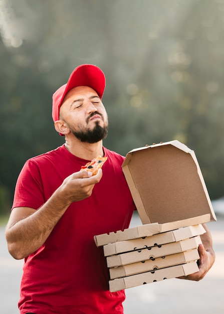Medium shot satisfied delivery guy eating pizza Free Photo