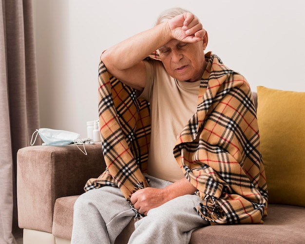 Medium shot sick man sitting on couch Premium Photo