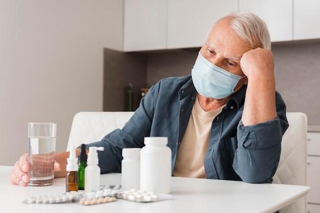 Medium shot sick man wearing medical mask Free Photo