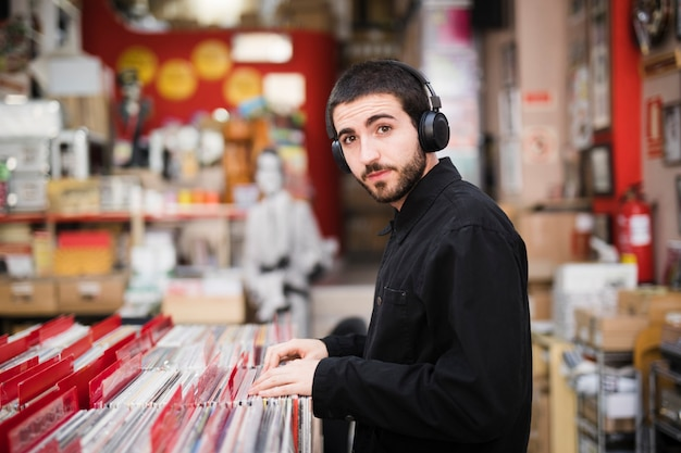 Medium shot side view of young man looking at camera in vinyl store Free Photo
