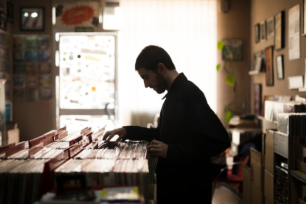 Medium shot side view of young man looking for vinyls in store Free Photo