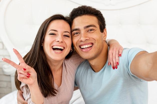 Medium shot smiley couple taking a selfie Free Photo