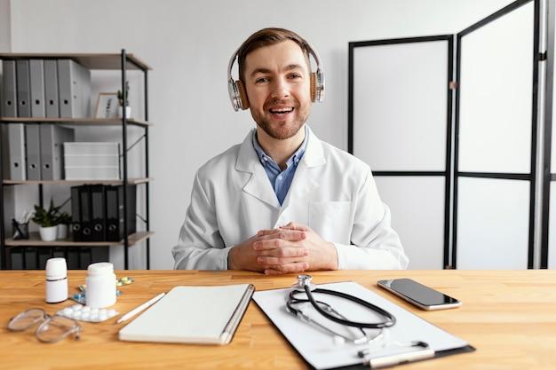 Medico di smiley del colpo medio alla scrivania Foto Gratuite