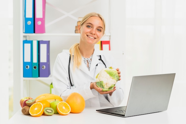 Medium shot smiley doctor with laptop and cauliflower Free Photo