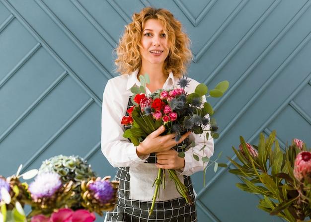 Medium shot smiley florist holding a bouquet of flowers Free Photo