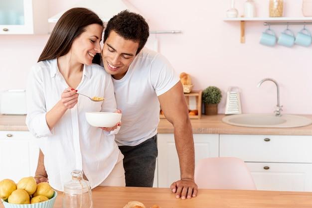 Ragazza di smiley del colpo medio che mangia prima colazione Foto Gratuite