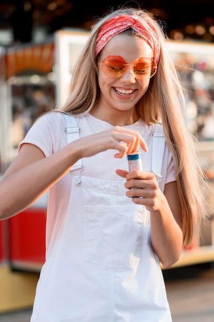 Ragazza di smiley colpo medio che produce palloncini di sapone Foto Gratuite