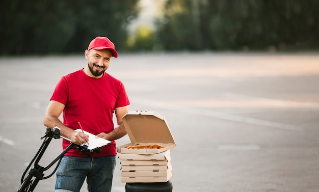 Medium shot smiley guy with pizza writing Free Photo