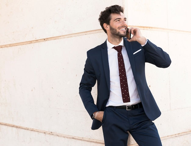 Medium shot smiley lawyer talking on the phone Free Photo