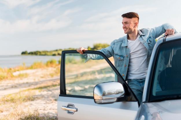 Medium shot smiley man posing with car Free Photo