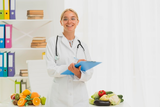 Medium shot smiley nutritionist with stethoscope Free Photo