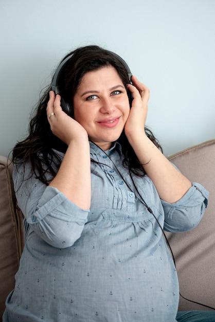 Medium shot smiley pregnant woman with headphones Free Photo