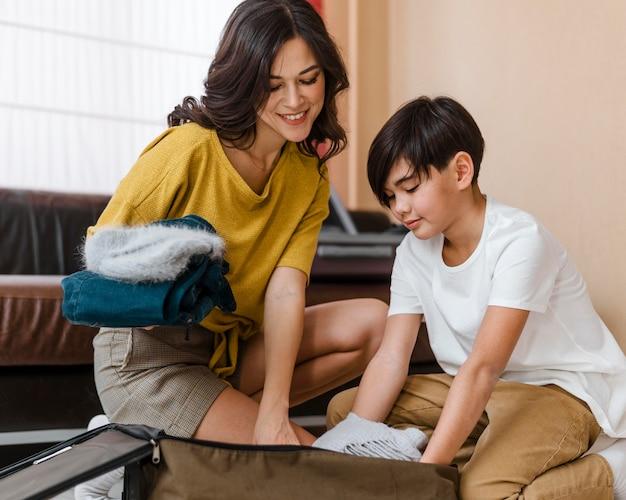 중간 샷 웃는 여자와 아이 포장 무료 사진