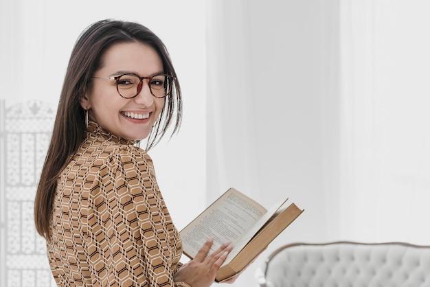 Medium shot smiley woman holding book Free Photo