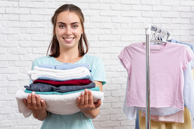 Medium shot smiley woman holding folded clothes and towels Free Photo