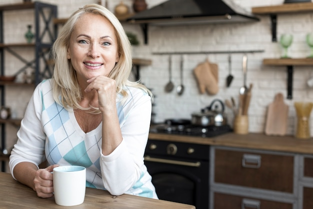 Medium shot smiley woman holding a mug Free Photo