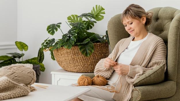 안락의 자에 뜨개질 중간 샷 웃는 여자 무료 사진
