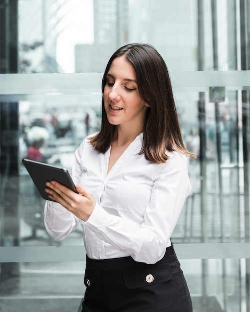 Medium shot smiley woman looking at her tablet Free Photo