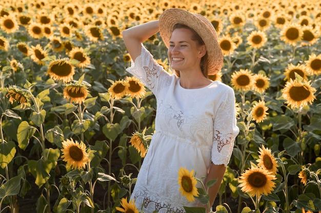 ミディアムショットのスマイリー女性が帽子でポーズ 無料写真