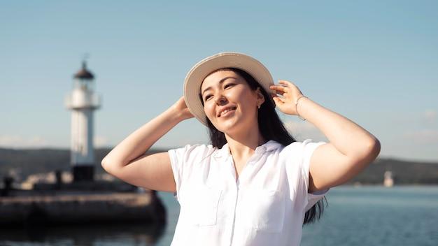 Улыбающаяся женщина среднего выстрела позирует в шляпе Бесплатные Фотографии