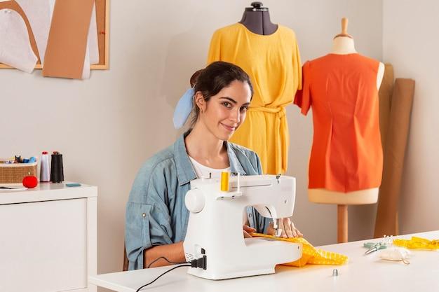 機械で縫うミディアムショットスマイリー女性 無料写真
