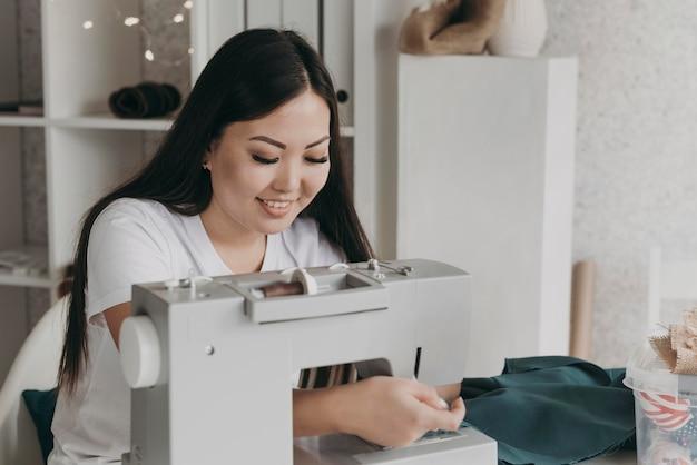중간 샷 웃는 여자 바느질 무료 사진