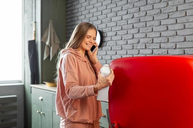 Medium shot smiley woman talking on phone Free Photo