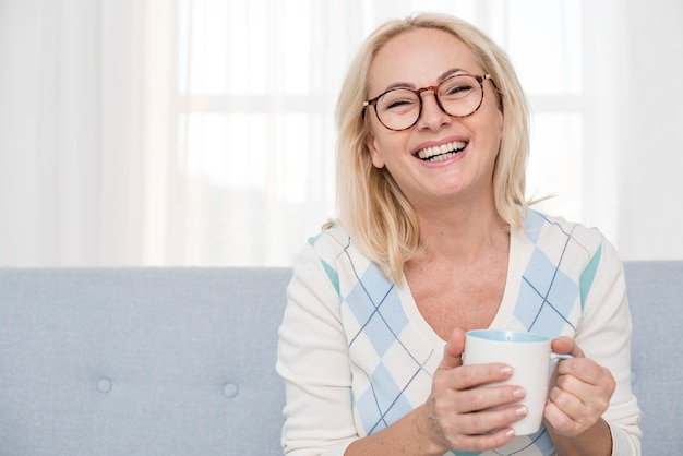 Medium shot smiley woman with mug on the couch Free Photo