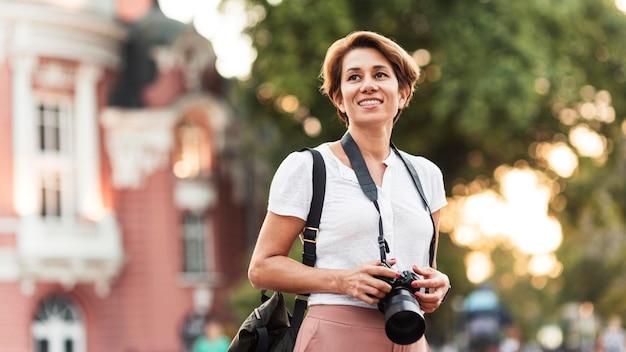 Улыбающаяся женщина среднего выстрела с фотоаппаратом Бесплатные Фотографии