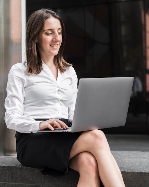 Средний выстрел смайлик женщина работает на ноутбуке Бесплатные Фотографии
