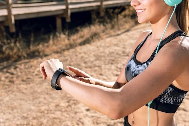 Medium shot sporty woman checking her smartwatch Free Photo