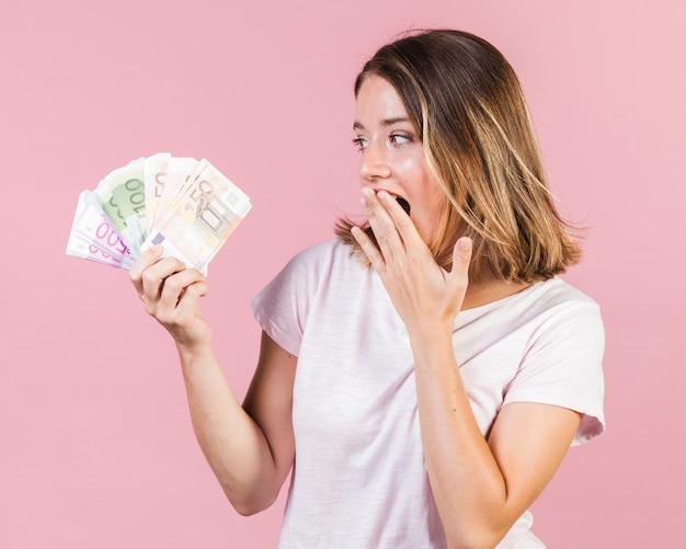 Medium shot surprised girl holding money Free Photo