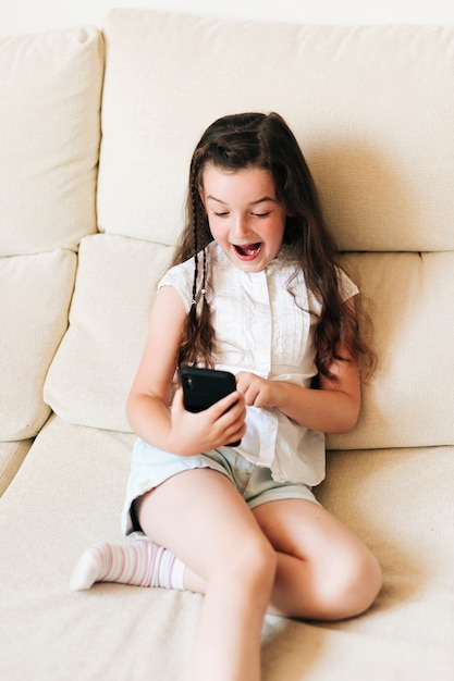 Medium shot surprised girl with phone on the couch Free Photo