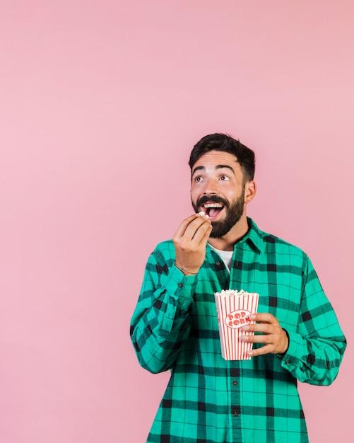 Medium shot surprised guy eating popcorn Free Photo