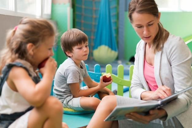 Medium shot teacher reading to kids Free Photo
