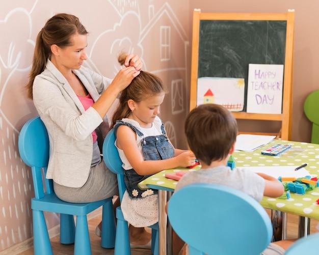 Учитель среднего кадра завязывает девушке волосы Бесплатные Фотографии