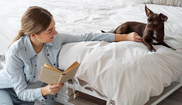 Средний снимок чтения подростка с собакой Бесплатные Фотографии