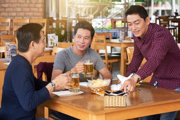 Medium shot of three friends having beer in bar Free Photo