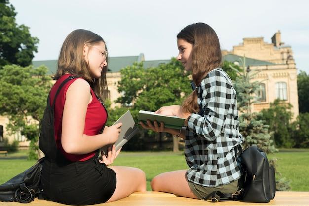 Medium shot of two highschool girls studying Free Photo