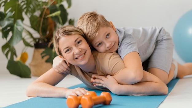 ミディアムショットの女性とヨガマットの子供 無料写真