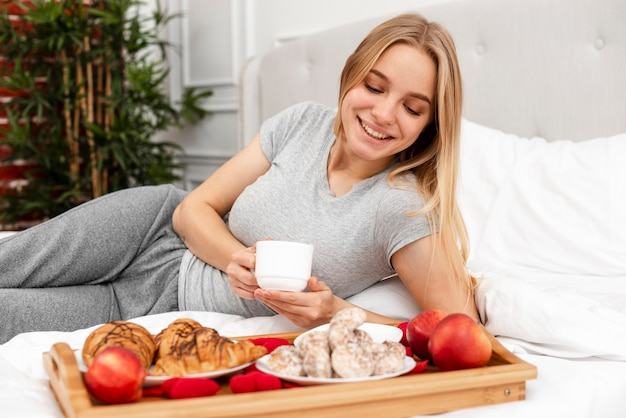Medium shot woman in bed with breakfast Free Photo