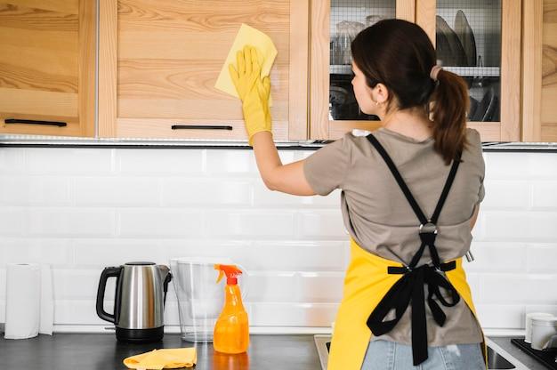 ミディアムショットの女性がキッチンを掃除 無料写真
