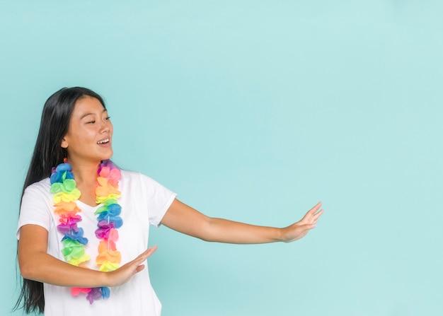 Medium shot of woman dancing with hawaiian flowers Free Photo