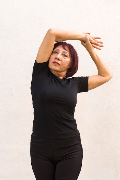 Medium shot of woman doing warm-up exercise Free Photo
